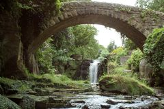 Under the bridge. Beautiful arch of the brige frames the waterfall Stock Photos