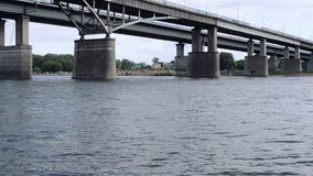 Under the Bridge. Gentle lapping flowing river called the White River in Ufa Bashkortostan Russia, with the central transport bridge in the background stock footage