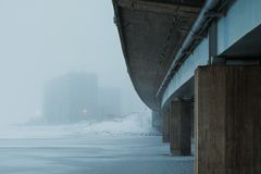 Under the bridge. Goes river with ice on it. Fog in background with construction site Royalty Free Stock Photo