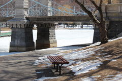 Under the bridge. Horizontal view of a city park bridge in winter with a walkway leading undeneath Stock Photography