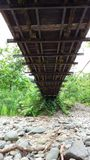 Under the bridge. Looking up at mossy bridge bottom from rocky ground Stock Photography