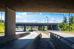 Under the bridge on the motorway. Concrete construction of road junction. Highway in Europe. Between two highways. No. Under the bridge on the motorway. Concrete stock photo