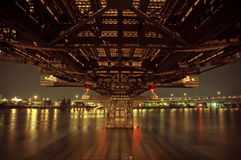 Under a Bridge At Night With City Lights Stock Photography