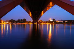 Under the bridge photo of street lights reflecting on the water after sunset Royalty Free Stock Image