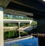 Under bridge. Reflection on water trees green blue stock photography