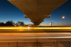 Under the bridge. Train in motion blue under the bridge at twilight Stock Image