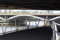 Under the Chelsea Bridge. View of the Thames and the railway bridge. Pedestrian bridge leading to Battersea Park royalty free stock image