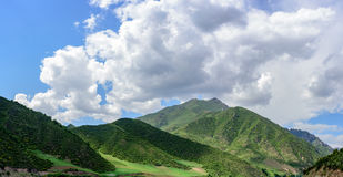 Under the clear weather, the blue sky, the white clouds, the green mountains make up the beautiful scenery. In Qinghai province of China, the beautiful scenery Royalty Free Stock Photos