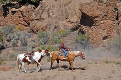 Under the cliffs. A young horseback rider leads a second horse wearing a saddle beneath cliffs of red rock Royalty Free Stock Photos