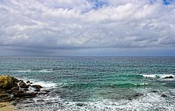CAlm, green and blue ocean near a rocky shore Royalty Free Stock Image