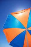Under colourful beach umbrella. Shade from the hot sun under a colourful blue and orange beach umbrella with blue sky Royalty Free Stock Photo