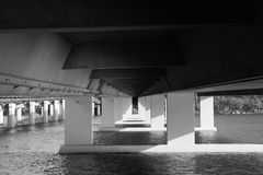 Under concrete bridge across river black and white. Black and white photo under a concrete bridge over a river. Beneath Hawkesbury River Bridge near Mooney Royalty Free Stock Image