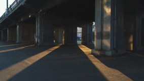 Under the concrete bridge through the spans the sunbeam shines brightly. In a deserted place at sunset, the sun sets and illuminates the asphalt area. A flash stock video footage