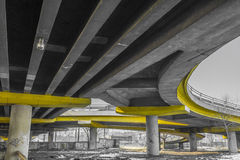 Under a concrete road bridge with yellow pillars Royalty Free Stock Images