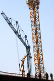 Under construction. Group of workers on roof of building.crane in background royalty free stock photography