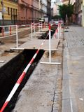 Under construction. A street under construction with red and white tape around a ditch Royalty Free Stock Images
