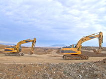 Under construction. Two diggers on way to work royalty free stock photo