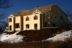 Under Construction. Exterior of a large, new house under construction in the winter Royalty Free Stock Photography