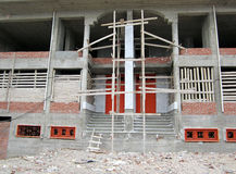 Under construction. Wooden door on front of new building under construction withe small windows and broken bricks in the street Stock Image
