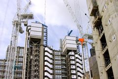 Under Construction. High-rise office buildings under construction, using large industrial cranes stock image