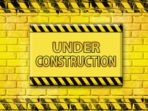 Under construction. In yellow and black with brick wall Stock Photography
