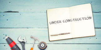 Under construction against tools and notepad on wooden background Stock Images
