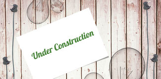 Under construction against wooden background with plugs Royalty Free Stock Images