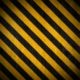 Under construction background. Traditional black and yellow warning background with grunge effect stock illustration