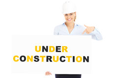 Under construction banner. A picture of a pretty woman in a hard hat showing a banner with under construction inscription Royalty Free Stock Image