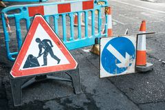 Under construction board sign on the closed road with arrow sign and traffic cone. Caution symbol under construction, work in. Progress sign stock images