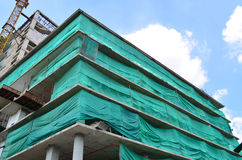 Under construction building covered with green net for safety Stock Photos