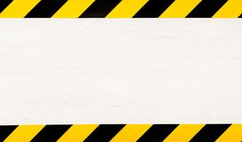 Under construction concept background. Warning tape. Under construction concept background. Warning tape frame on white wooden surface background with copy stock photos