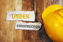 Under construction concept with protective yellow hard hat helme. T on wooden desk Royalty Free Stock Images