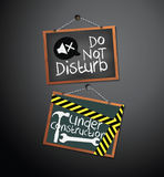 Under construction and do not disturb Signs on blackboard hanging with chain Stock Images