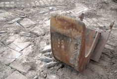 Excavator bucket at a construction site. With soil and broken paving stones royalty free stock photos