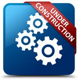 Under construction (gears icon) blue square button red ribbon in Stock Photo