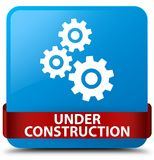 Under construction (gears icon) cyan blue square button red ribb Royalty Free Stock Photos