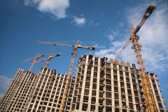 Under construction houses with cranes Royalty Free Stock Images