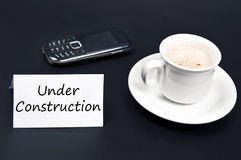 Under construction message on desk with coffee Stock Photography