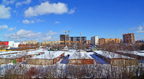 Under construction multi-storey building on  background of single-storey houses Royalty Free Stock Photography