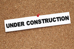 UNDER CONSTRUCTION. Note pinned on cork noticeboard Stock Photos