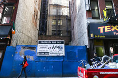 Under construction in NY. New York City, USA - May 19, 2014: Building site in lower manhattan. Narrow gap between two buildings. In the front a woman walks by Stock Photos