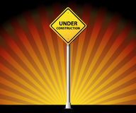 Under construction road sign on rays background Stock Image