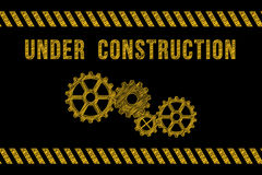 Under construction road sign in yellow on black with stripes Royalty Free Stock Image