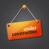 Under construction sign. Hung on a textured background Stock Image