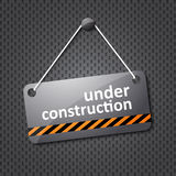 Under construction sign. Hung on a textured background Royalty Free Stock Photo