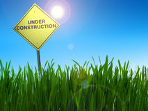 Under construction sign. With sun in the blue sky and green field stock photography
