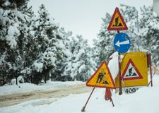 Under construction signs in snow. Snowy road and forest background. Royalty Free Stock Photo