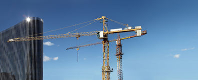 Under construction site building with crane and glass skyscraper. In the blue sky, business success concept Royalty Free Stock Photography