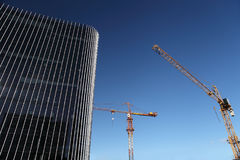 Under construction site building with crane and glass skyscraper. In the blue sky, business success concept Royalty Free Stock Photos